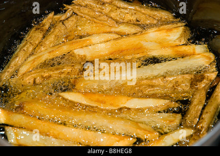 French Fries Cooking in Oil - Stock Photo