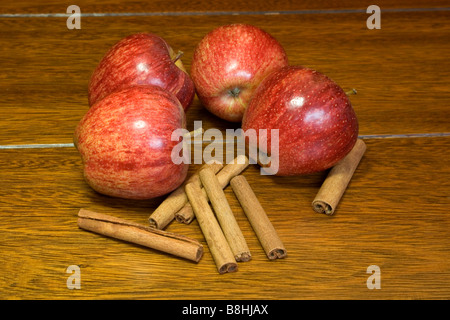 Fresh red apples and cinnamon sticks on wooden table - Stock Photo