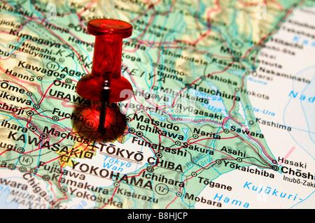 Red pushpin on an atlas Tokyo - Stock Photo