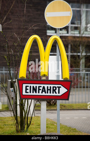 McDonalds sign at parking lot entrance from restaurant, no entry sign behind - Stock Photo