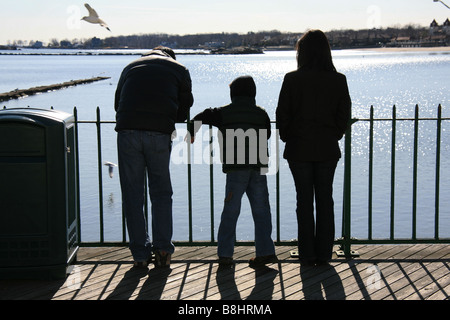 Young family in silhouette on a boardwalk by the sea. - Stock Photo