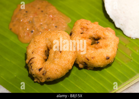India Tamil Nadu Kumbakonam South Indian breakfast two vadai served with spicy sambar and chutney served on banana - Stock Photo