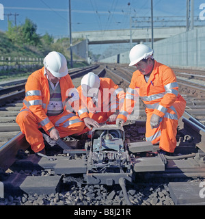 Contractors carrying out essential maintenance to an electrical points mechanism on a high speed railway system. - Stock Photo
