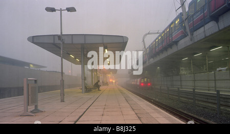 Misty early morning at Jubilee Line Extension's Canning Town station with Docklands Light Rail train on elevated - Stock Photo
