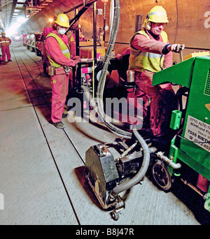 Cutting grooves in concrete floor of the Channel Tunnel service tunnel prior to installing guidance wires for the - Stock Photo