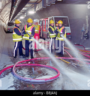 Firefighters testing fire suppression equipment in the Channel Tunnel service tunnel - emulsifier in the water produces - Stock Photo