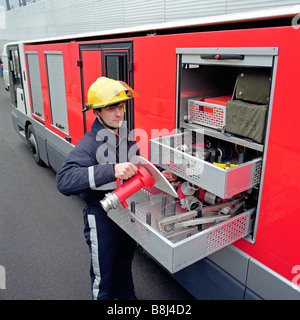Firefighter selects equipment from a specially designed STTS vehicle in the Channel Tunnel service tunnel. - Stock Photo