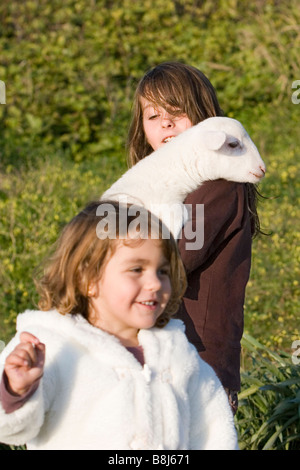 children playing with a sheep - Stock Photo