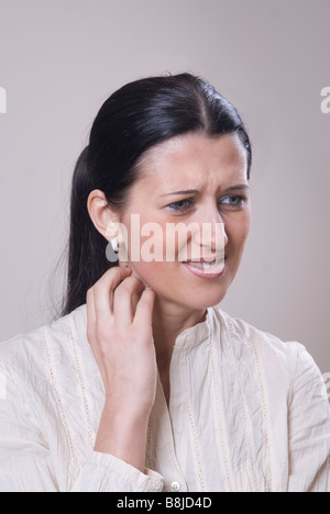 Woman scratching neck - Stock Photo