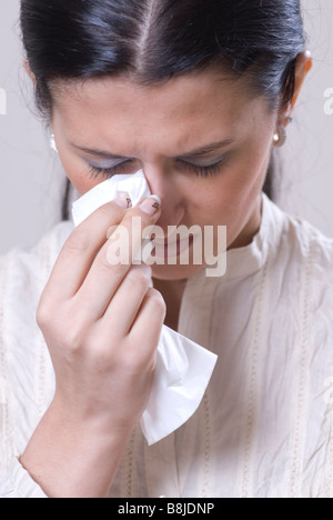 Woman crying and wiping tears with tissue - Stock Photo