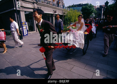 Wedding Bride in western style dress sitting in rickshaw Being pulled by bridegroom Photographer SHANGHAI CHINA - Stock Photo