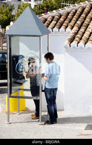 Woman using a public telephone on a spanish street corner - Stock Photo
