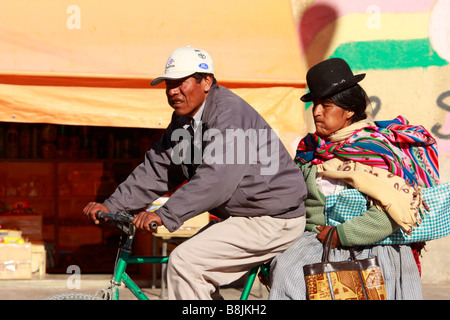 A man and a woman are cycling on the street in Uyuni Bolivia - Stock Photo