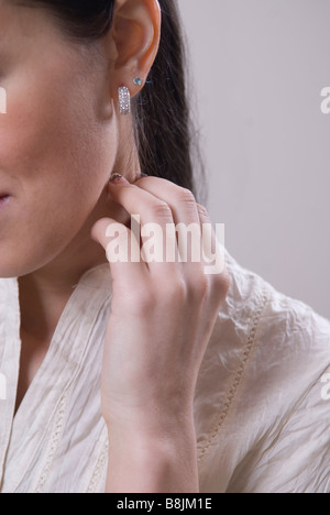 Close up of a young woman touching neck - Stock Photo