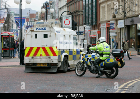 PSNI motocycle police man and armoured land rover riot vehicle close off road for St Patricks Day parade Belfast - Stock Photo