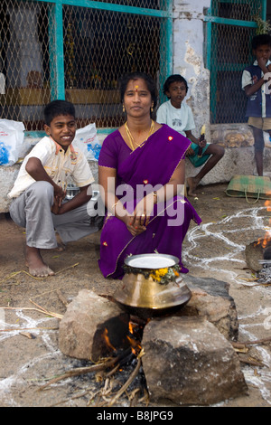 India Tamil Nadu Madurai Thiruchuli Village harvest festival woman cookign Pongal on open fire - Stock Photo