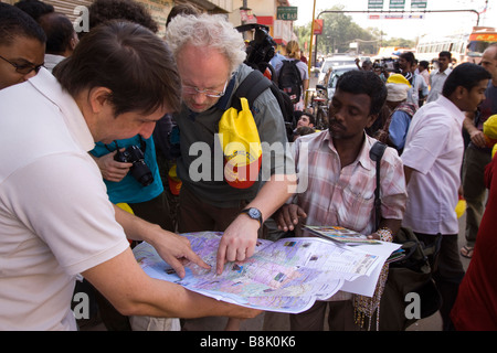 India Tamil Nadu Madurai lost foreign tourists looking at street hawkers map - Stock Photo