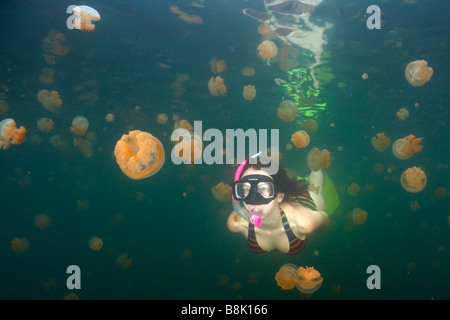 Young teenage girl swimming under the water surface in the famous Jellyfish lake on Rock isalnds of Palau - Stock Photo