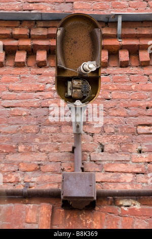 Old broken lantern with shattered bulb over red brick wall. - Stock Photo