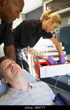 Paramedics with patient in ambulance Stock Photo