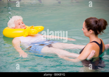 Instructor And Elderly Patient Undergoing Water Therapy - Stock Photo