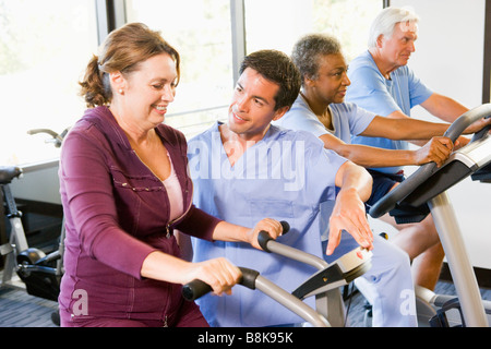 Nurse With Patient In Rehabilitation Using Exercise Machine - Stock Photo