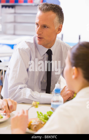 Students and teacher having lunch in dining hall - Stock Photo