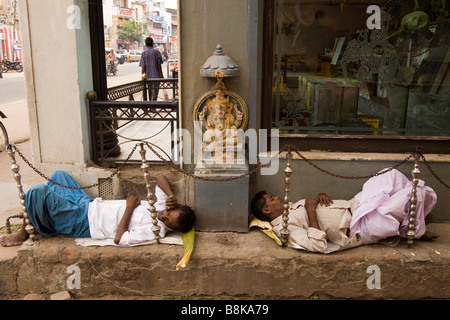 India Tamil Nadu Madurai two men sleeping in street next to small Hindu Sri Ganesh shrine - Stock Photo