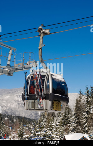 A gondola car over the Whistler Village on sunny winter day Whistler BC Canada - Stock Photo