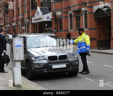 Traffic Warden Civil Enforcement Officer photographing the tax disc of a car in Birmingham West Midlands after issueing - Stock Photo