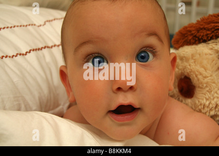 Blue eyed 8 month old baby boy looking at camera smiling - Stock Photo
