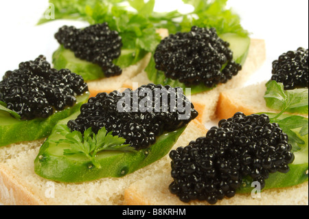 Sandwiches with black caviar and a cucumber on a white background - Stock Photo