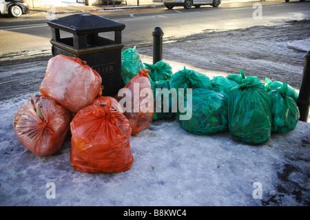Refuse bags piled up on a snow covered pathway next to a bin in Wimbledon Village, south west London, UK. - Stock Photo