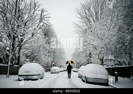 A commuter with umbrella makes his way to work on a snowy winter's morning in East Putney, London, UK. - Stock Photo
