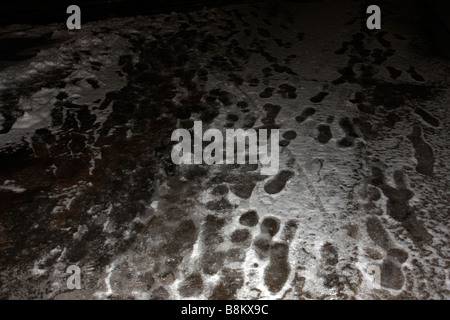 Footprints in snow and ice on pavement concrete in dark - Stock Photo