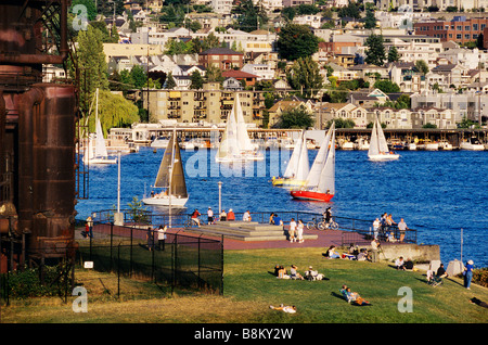 USA, Washington State, Seattle. Sailboats on Lake Union pass rusty gas conversion relics at Gas Works Park. - Stock Photo