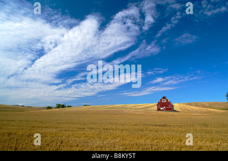 Red barn in the rolling farm country of the Palouse area of eastern Washington state - Stock Photo