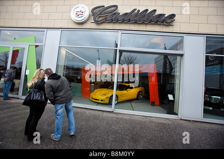 A couple look at a new car at Chevrolet Corvette dealership in Hamburg, Germany - Stock Photo