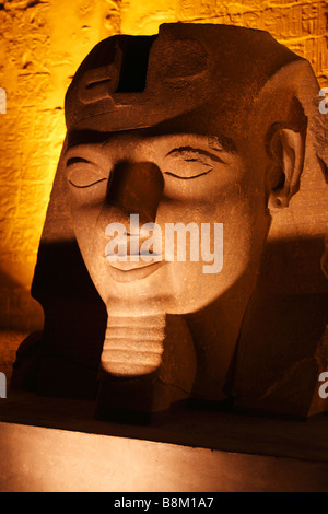Large stone carved head of Pharaoh Ramesses II at entrance to Luxor Temple illuminated at night, 'close up' detail, - Stock Photo
