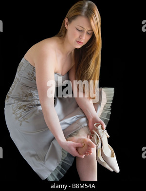 Young woman in a party dress. She has taken her shoes off and is massaging her sore feet. - Stock Photo