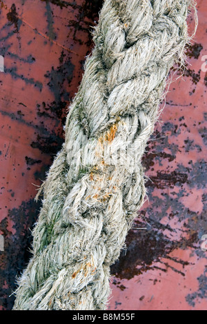 Old stron towing cable over scratched rusty ship hull background. - Stock Photo