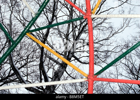 View through multicoloured out of focus fence to leafless winter birch branches over cloudy white sky. - Stock Photo