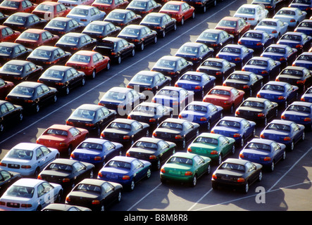 New cars sit in rows on dock after being unloaded from ship economy oil mileage market sell overload inventory auto - Stock Photo