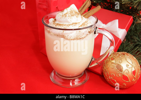 A frothy mug of eggnog under the Christmas tree Red background with room for text