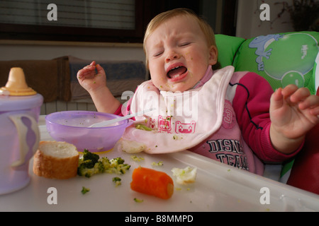 One year old baby girl crying in highchair at meal time - Stock Photo