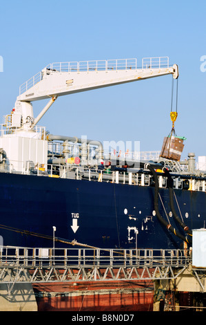 Crane loading pallet of supplies or provisions on ship and oil being offloaded by black hoses from oil tanker with - Stock Photo