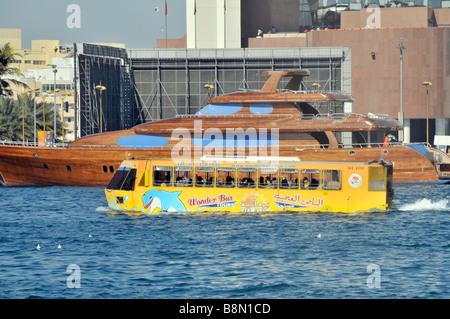 Dubai Creek amphibious tour boat bus and waterfront - Stock Photo