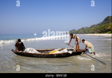 India Andaman and Nicobar Havelock island Radha Nagar beach launching fishing boat through the surf - Stock Photo