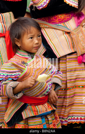 Portrait of a Flower H'mong girl dressed in traditional costume of the ethnic minority group in Bac Ha, Vietnam. - Stock Photo