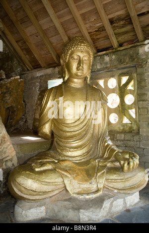Statue of Buddha facing the central square or piazza in the Italianate village of Portmeirion in Snowdonia, North - Stock Photo